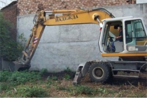 "The excavator begins digging. The word on its side is ""hope"" in Bulgarian."