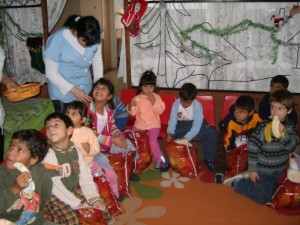 Abandoned children enjoying the Christmas presents and the fruits.